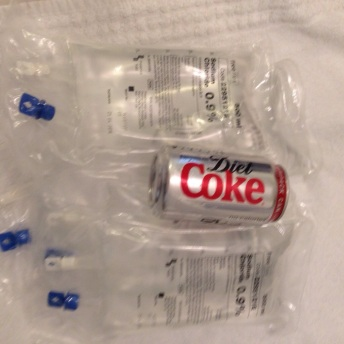 Picture showing a can of diet coke resting on top of a pile of IV fluid bags