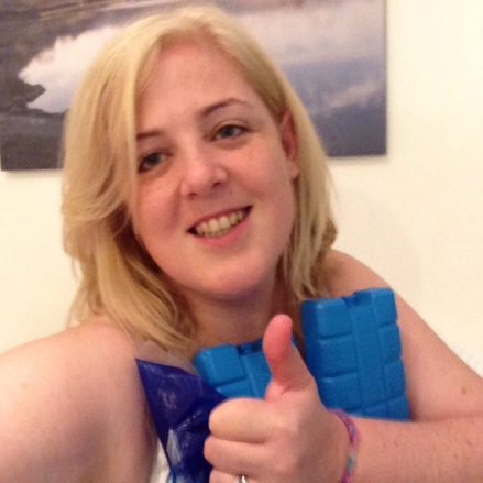I'm giving a thumbs up to the camera, and hugging three ice packs to my chest