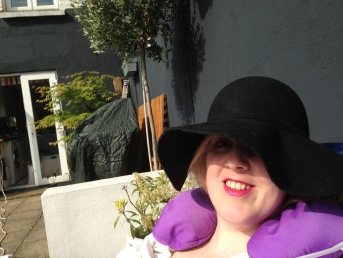 I'm relaxing in the shade - lying down with my purple neck cushion around my neck and a large floppy black hat, which almost completely covers my face